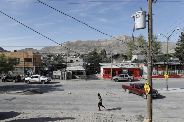 In this July 31, 2019, photo, Alphat, of Uganda, runs through a neighborhood surrounding the El Buen Pastor shelter for migrants in Cuidad Juarez, Mexico. Alphat runs relentlessly, and seemingly effortlessly. People stop to stare, surprised to see a black man with ham-sized biceps and impossibly broad shoulders running through this city, which has long been a magnet for migrants. (AP Photo/Gregory Bull)