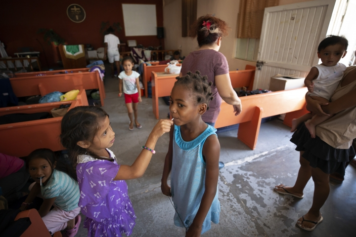 In this July 25, 2019, photo, a Honduran girl shares a lollipop with an African girl at El Buen Pastor shelter for migrants in Cuidad Juarez, Mexico. (AP Photo/Gregory Bull)