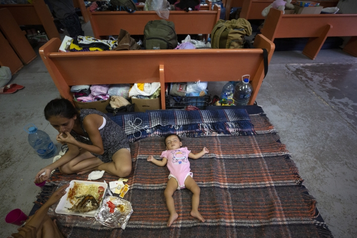 In this July 28, 2019, photo, Evelyn, of El Salvador, eats a shared lunch as her daughter sleeps an area set up for families among the pews at El Buen Pastor shelter for migrants in Cuidad Juarez, Mexico. (AP Photo/Gregory Bull)