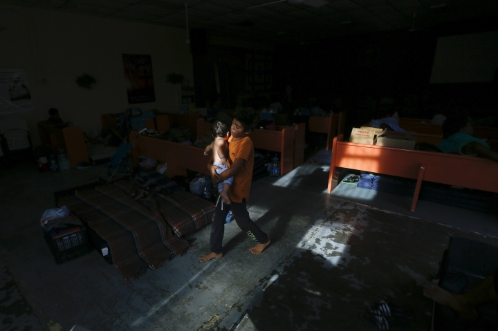 In this July 28, 2019, photo, Anderson Jimenez, of El Salvador, carries his brother Jacob at El Buen Pastor shelter for migrants in Cuidad Juarez, Mexico. (AP Photo/Gregory Bull)