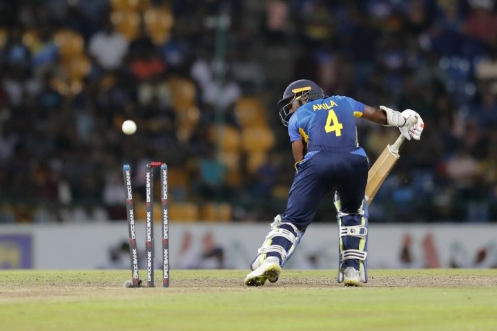 Sri Lanka's Akila Dananjaya looks at his wicket after being bowled out by New Zealand's Scott Kuggeleijn during the third Twenty20 international cricket match between Sri Lanka and New Zealand in Pallekele, Sri Lanka, Friday, Sept. 6, 2019. (AP Photo/Eranga Jayawardena)