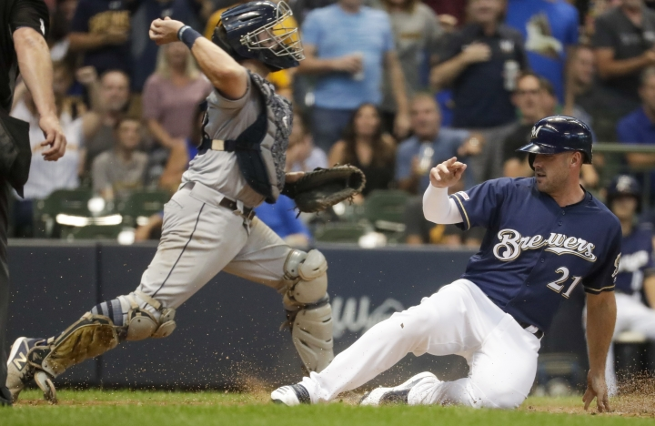 Milwaukee Brewers' Travis Shaw scores as San Diego Padres catcher Austin Hedges makes a throw to third on a ball hit by Trent Grisham during the sixth inning of a baseball game Thursday, Sept. 19, 2019, in Milwaukee. (AP Photo/Morry Gash)