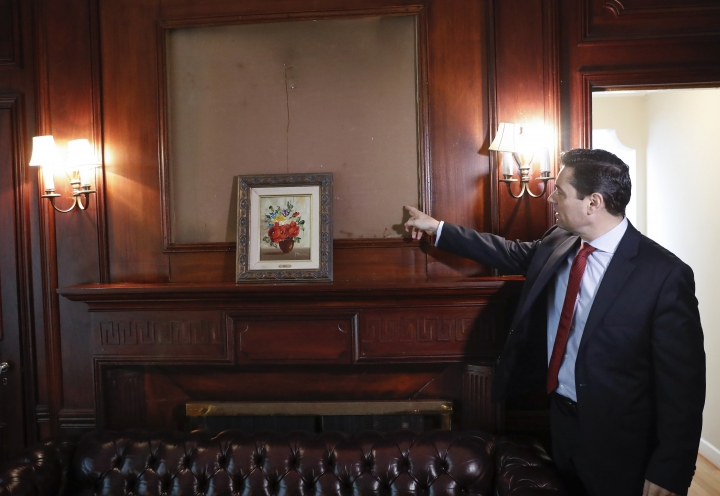 In this Sept. 17, 2019, photo, Carlos Vecchio, an exiled politician who the U.S. recognizes as Venezuela's ambassador, points to an area above the fireplace where artwork once hung inside the Ambassador's residence in Washington. U.S. officials are investigating the possible looting from Venezuela of valuable European and Latin American artwork they believe is being quietly plundered by government insiders as Nicolas Maduro struggles to keep his grip on power. (AP Photo/Pablo Martinez Monsivais)