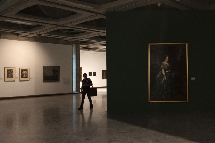In this Sept. 17, 2019, photo, a woman walks between European paintings in the dark in the Museum of Fine Arts of Caracas, Venezuela. Only about a third of the 18 galleries are open to the public; the rest have been closed for months due to renovations, although there's no sign any are taking place. (AP Photo/Andrea Hernandez Briceño)