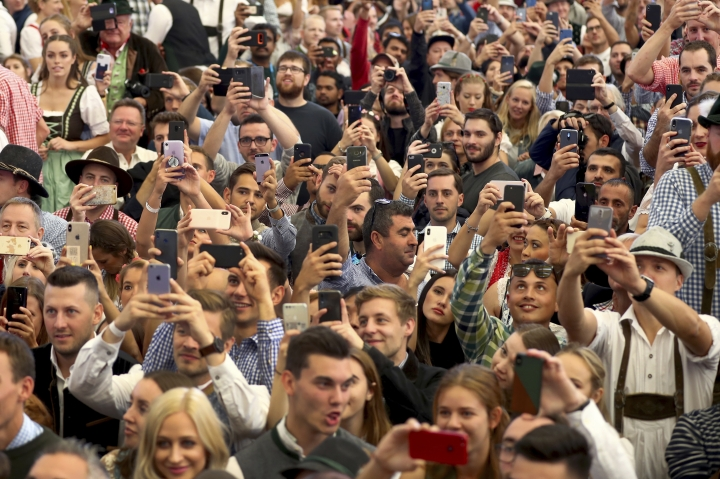 Visitors hold smartphones during the opening of the 186th 'Oktoberfest' beer festival in Munich, Germany, Saturday, Sept. 21, 2019. (AP Photo/Matthias Schrader)