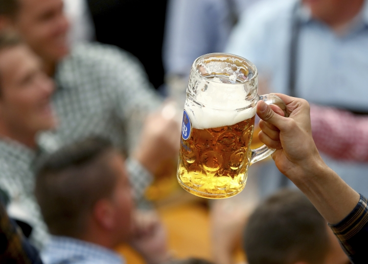 A guest holds glasses of beer during the opening of the 186th 'Oktoberfest' beer festival in Munich, Germany, Saturday, Sept. 21, 2019. (AP Photo/Matthias Schrader)