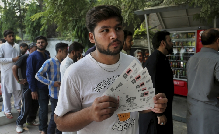 A fan displays tickets of an upcoming cricket match between Pakistan and Sri Lanka while others waiting for their turn outside a bank in Lahore, Pakistan, Saturday, Sept. 21, 2019. Pakistan recalled all-rounders Iftikhar Ahmed and Mohammad Nawaz for three-match one-day international series against Sri Lanka, starting at Karachi from next week. (AP Photo/K.M. Chaudary)