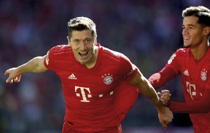 Bayern's Robert Lewandowski, left, celebrates after scoring the opening goal during the German Bundesliga soccer match between FC Bayern Munich and 1. FC Cologne in Munich, Germany, Saturday, Sept. 21, 2019. (AP Photo/Matthias Schrader)