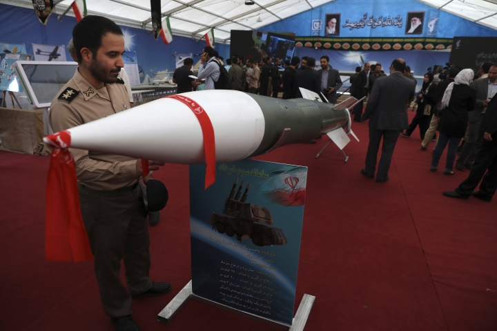 "An Iranian army member looks at a missile in an exhibition in which the Revolutionary Guard also displays pieces of the American drone Global Hawk shot down by the Guard in the Strait of Hormuz in June 2019, in Tehran, Iran, Saturday, Sept. 21, 2019. Iran's powerful Revolutionary Guard is ready for combat and ""any scenario,"" its chief commander said Saturday, as the country's nuclear deal with world powers collapses and the U.S. alleged Iran was behind a weekend attack on major oil sites in Saudi Arabia that shook global energy markets. (AP Photo/Vahid Salemi)"