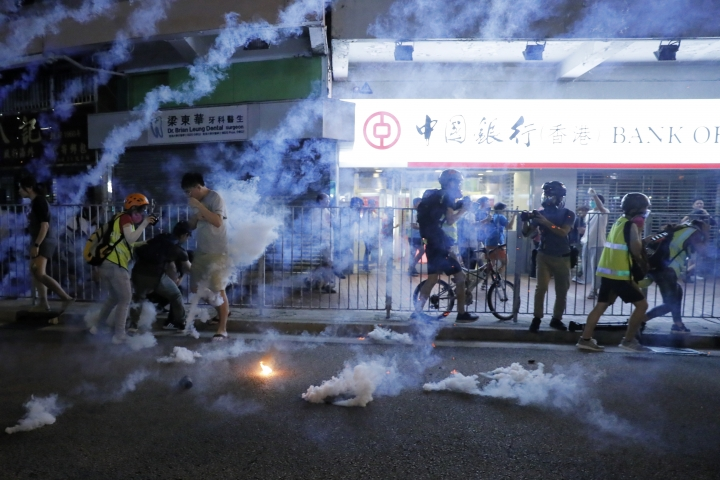 Tear fas fills the street as protesters continue to battle with police on the streets of Hong Kong on Saturday, Sept. 21, 2019. Protesters in Hong Kong threw gasoline bombs and police fired tear gas Saturday in renewed clashes over anti-government grievances (AP Photo/Kin Cheung)