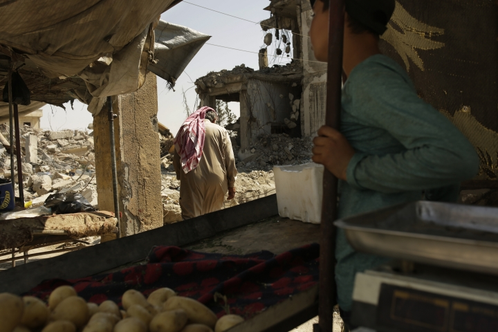 In this Thursday, Sept. 5, 2019, photo, a man passes through a vegetable stand on the way to his heavily damaged home in Raqqa, Syria. Officials say more than 800,000 people have returned to the city and its adjacent suburbs_ nearly eight times the residents who were left when Islamic State militants were finally expelled from its stronghold in Oct. 2017. (AP Photo/Maya Alleruzzo)