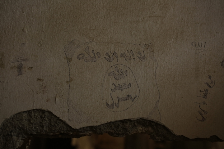 In this Thursday, Sept. 5, 2019, photo, a prisoner's drawing of the Islamic State militant flag remains on the wall of a makeshift IS prison in the basement off the main stadium in Raqqa, Syria. (AP Photo/Maya Alleruzzo)