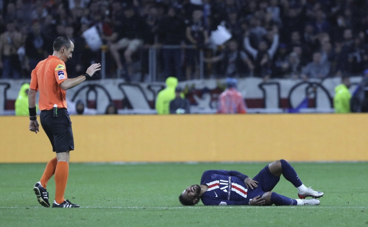 Referee Ruddy Buquet, left, looks at PSG's Neymar who lies injured on the pitch during the French League 1 soccer match between Lyon and Paris SG, at the Stade de Lyon in Decines, outside Lyon, France, Sunday, Sept. 22, 2019. (AP Photo/Laurent Cipriani)