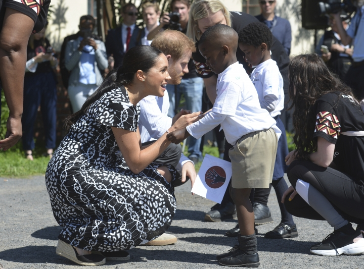 Britain's royal couple Prince Harry and Meghan Duchess of Sussex, greet children on their arrival at the Nyanga Methodist Church in Cape Town, South Africa, Monday, Sept, 23, 2019, which houses a project where children are taught about their rights, self-awareness and safety, and are provided self-defence classes and female empowerment training to young girls in the community. The royal couple are starting their first official tour as a family with their infant son, Archie (Courtney Africa / Africa News Agency via AP, Pool)