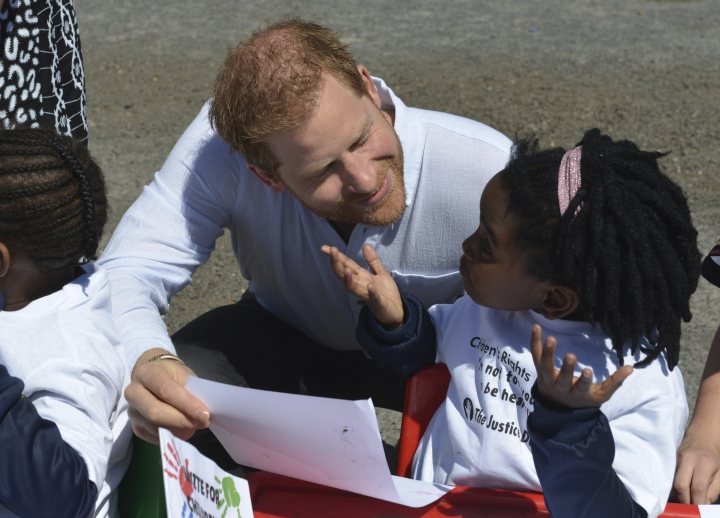 His Royal Higness Prince Harry greets children on his arrival at the Nyanga Methodist Church in Cape Town, South Africa, Monday, Sept, 23, 2019, which houses a project where kids are taught about their rights, self-awareness and safety, and are provided self-defence classes and female empowerment training to young girls in the community. The royal couple are starting their first official tour as a family with their infant son, Archie (Courtney Africa / Africa News Agency via AP, Pool)