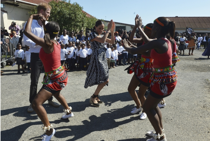 Britain's royal couple Prince Harry and Meghan Duchess of Sussex, move with dancers on their arrival at the Nyanga Methodist Church in Cape Town, South Africa, Monday, Sept, 23, 2019, which houses a project where children are taught about their rights, self-awareness and safety, and are provided self-defence classes and female empowerment training to young girls in the community. The royal couple are starting their first official tour as a family with their infant son, Archie (Courtney Africa / Africa News Agency via AP, Pool)