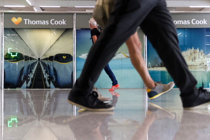 Passengers walk past a closed Thomas Cook office at Palma de Mallorca airport on Monday Sept. 23, 2019. Spain's airport operator AENA says that 46 flights have been affected by the collapse of the British tour company Thomas Cook, mostly in the Spanish Balearic and Canary archipelagos. (AP Photo/Francisco Ubilla)