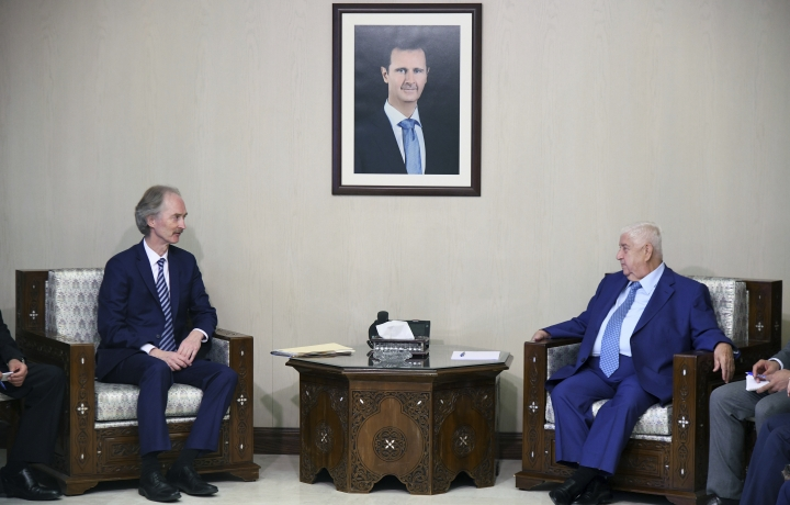"""In this photo released by the Syrian official news agency SANA, the U.N.'s special envoy for Syria Geir Pedersen, left, meets with Syrian Foreign Minister Walid al-Moallem, in Damascus, Syria, Monday, Sept. 23, 2019. Syria's state news agency SANA said Monday that al-Moallem discussed the formation of a constitutional committee and its work with Pedersen. SANA said al-Moallem's meeting with Pedersen on Monday focused on the committee's setup and guarantees that it be free """"from any foreign intervention."""" (SANA via AP)"""