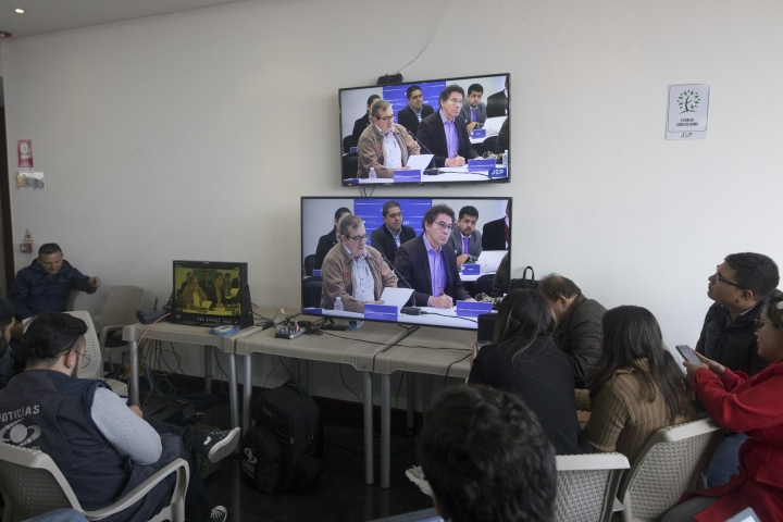 Journalists watch former rebel leaders' appearance before Colombia's special peace tribunal to testify in an ongoing probe of their role in civilian kidnappings in Bogota, Colombia, Monday, Sept. 23, 2019. (AP Photo/Ivan Valencia)