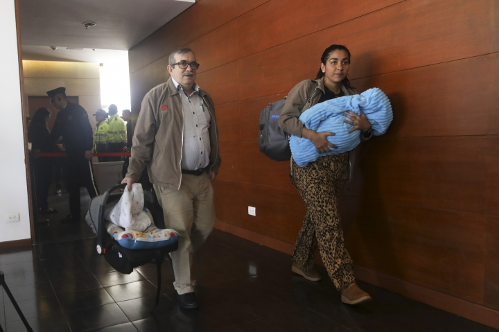 Accompanied by his wife Johana Castro and their child, former rebel leader commander Rodrigo Londono arrives to appear before Colombia's special peace tribunal to testify in an ongoing probe of their role in civilian kidnappings in Bogota, Colombia, Monday, Sept. 23, 2019. Londono, also know by his alias Timochenko, was the FARC's top military commander and now heads its legal political party. (AP Photo/Ivan Valencia)