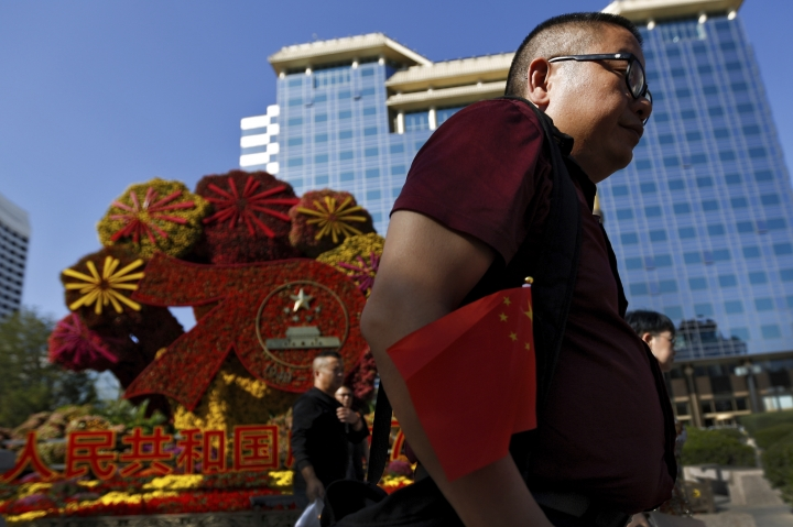 "A man carrying a national flag walks with his colleagues past by a floral decoration for the 70th anniversary of the founding of the People's Republic of China, on display along Chang'an street in Beijing, Tuesday, Sept. 24, 2019. China's central bank governor says policy will stay ""stable and healthy,"" suggesting Beijing has no plans to join the United States and Europe in cutting interest rates to stimulate economic growth. (AP Photo/Andy Wong)"