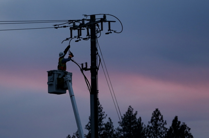 FILE - In this Nov. 26, 2018, file photo, a Pacific Gas & Electric lineman works to repair a power line in fire-ravaged Paradise, Calif. PG & E anticipates shutting off power in 9 California counties due to hot, dry and windy conditions even as it formalizes settlements with the vast majority of claims from the deadly Northern California wildfires in 2017 and 2018. The San Francisco utility will make a final decision before noon Monday, Sept. 23, 2019, on whether it will cut power. (AP Photo/Rich Pedroncelli, File)