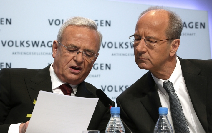 FILE - In this March 13, 2014 file photo then Volkswagen CEO Martin Winterkorn, left, and then CFO Hans Dieter Poetsch, right, talk prior to the company's annual press conference in Berlin, Germany. German prosecutors say they have charged Volkswagen chief executive Herbert Diess and chairman Hans Dieter Poetsch, along with former CEO Martin Winterkorn, with market manipulation in connection with the diesel emissions scandal that erupted in 2015. (AP Photo/Michael Sohn, file)