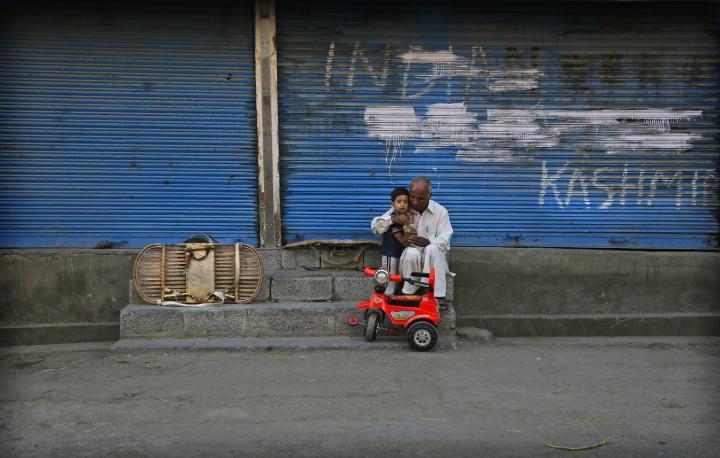 In this Tuesday, Sept. 17, 2019, photo, a man feeds a child outside a closed shop during curfew hours in Srinagar, Indian controlled Kashmir. As the disputed Himalayan region continues to reel under this unprecedented lockdown, the children of the region have been the most affected. Although some restrictions have been eased in the main city of Srinagar, schools in the region continue to remain closed. (AP Photo/Mukhtar Khan)