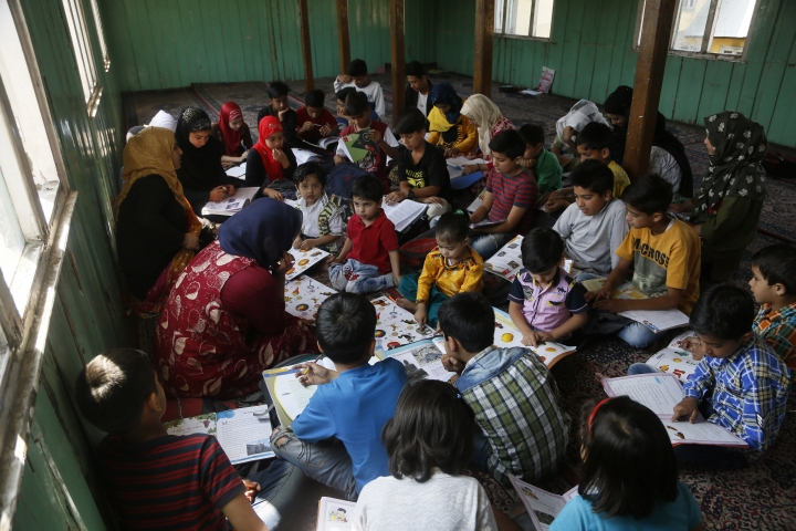 In this Thursday, Sept. 19, 2019, photo, children study inside a local mosque building during free coaching classes by locals in Srinagar, Indian controlled Kashmir. Kashmir's children have found refuge in makeshift schools amid the lockdown as dozens of ad hoc learning centers have popped up in homes and religious centers, and hundreds of students have signed up. (AP Photo/Mukhtar Khan)