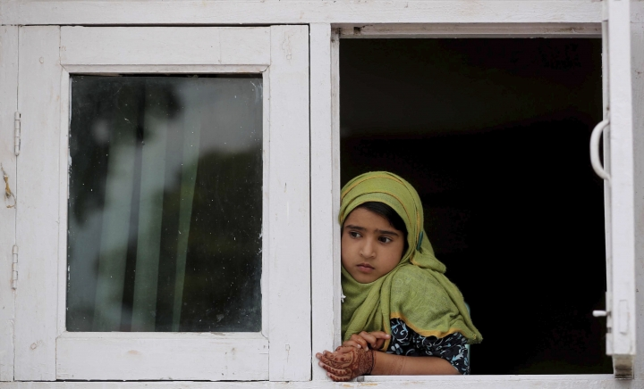 FILE- In this Friday, Aug. 30, 2019, file photo, a child watches a protest from the window of a shrine in Srinagar, Indian controlled Kashmir. As the disputed Himalayan region continues to reel under this unprecedented lockdown, the children of the region have been the most affected. Although some restrictions have been eased in the main city of Srinagar, schools in the region continue to remain closed. (AP Photo/Mukhtar Khan, file)