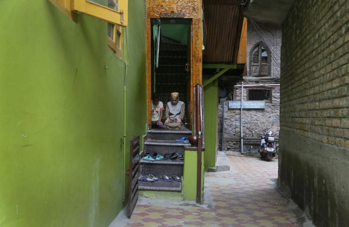 FILE- In this Friday, Aug. 16, 2019, file photo, Muslim boys offer Friday prayers at the doorway of a local mosque in an alley during curfew-like restrictions in Srinagar. As the disputed Himalayan region continues to reel under this unprecedented lockdown, the children of the region have been the most affected. (AP Photo/Mukhtar Khan, file)