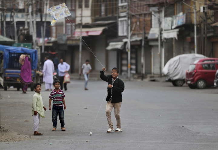 In this Tuesday, Sept. 17, 2019, photo, a Kashmiri child flies a kite outside his home in Srinagar, Indian controlled Kashmir. As the disputed Himalayan region continues to reel under this unprecedented lockdown, the children of the region have been the most affected. Reports from the region also suggest that children, some as young as 14, have been injured in the government forces' action. (AP Photo/Mukhtar Khan)