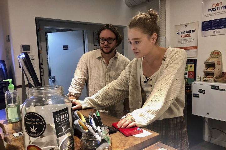 """In this photo taken Sept. 20, 2019, David Alport, owner of the Bridge City Collective marijuana dispensary in Portland, Ore., goes over sales numbers with the store's general manager Cameron Moore. The company has seen a 31% decrease in its sales of vaping products in the past two weeks. """"It's having an impact on how consumers are behaving,"""" said Alport. """"People are concerned, and we're concerned."""" (AP Photo/Gillian Flaccus)"""
