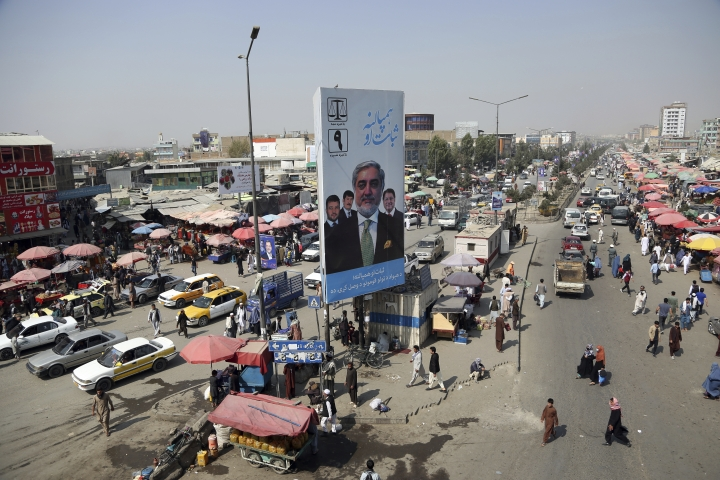 In this Tuesday, Sept. 24, 2019 photo, a campaign poster for the upcoming presidential elections is displayed in Kabul, Afghanistan. Millions of Afghans are expected to go to the polls on Saturday to elect a new president, despite an upsurge of violence in the weeks since the collapse of a U.S.-Taliban deal to end America's longest war, and the Taliban warning voters to say away from the polls. (AP Photo/Rahmat Gul)