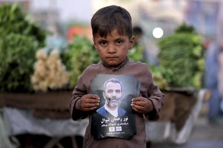 In this Monday, Sept. 23, 2019 photo, a child who works in the bazar holds a poster of presidential candidate Noor Rahman Liwal, on the outskirts of Kabul, Afghanistan. Millions of Afghans are expected to go to the polls on Saturday to elect a new president. It is estimated the polls and a potential second round of voting -- held if the first round is inconclusive -- will cost $150 million. (AP Photo/Ebrahim Noroozi)
