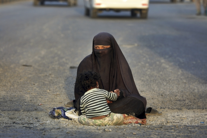 In this Monday, Sept. 23, 2019, a woman waits for alms as she sits with her child in a street on the outskirts of Kabul, Afghanistan. Millions of Afghans are expected to go to the polls on Saturday to elect a new president. It is estimated the polls and a potential second round of voting -- held if the first round is inconclusive -- will cost $150 million. (AP Photo/Ebrahim Noroozi)