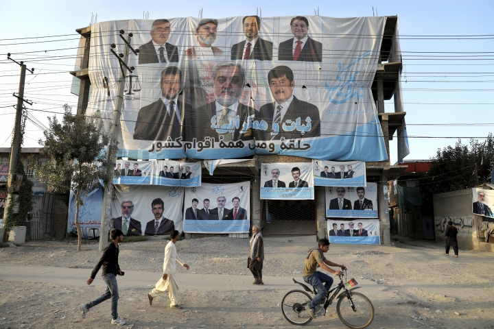 In this Monday, Sept. 23, 2019 photo, election posters for presidential candidate Abdullah Abdullah are draped over an building under construction, on the outskirts of Kabul, Afghanistan. Millions of Afghans are expected to go to the polls on Saturday to elect a new president, despite an upsurge of violence in the weeks since the collapse of a U.S.-Taliban deal to end America's longest war, and the Taliban warning voters to say away from the polls. (AP Photo/Ebrahim Noroozi)