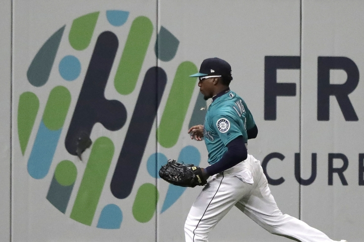 Seattle Mariners left fielder Shed Long runs next to a graphic on the outfield wall after catching a line-out by Oakland Athletics' Marcus Semien during the sixth inning of a baseball game, Friday, Sept. 27, 2019, in Seattle. (AP Photo/Ted S. Warren)