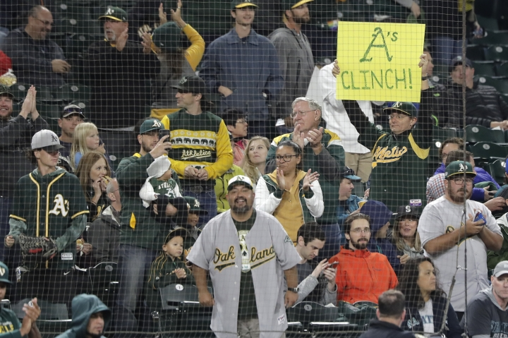 "A fan holds a sign that reads ""A's Clinch!"" during the first inning of a baseball game against the Seattle Mariners, Friday, Sept. 27, 2019, in Seattle. The Athletics clinched a wild-card berth in the American League before the first pitch of their game when the Cleveland Indians lost to the Washington Nationals. (AP Photo/Ted S. Warren)"