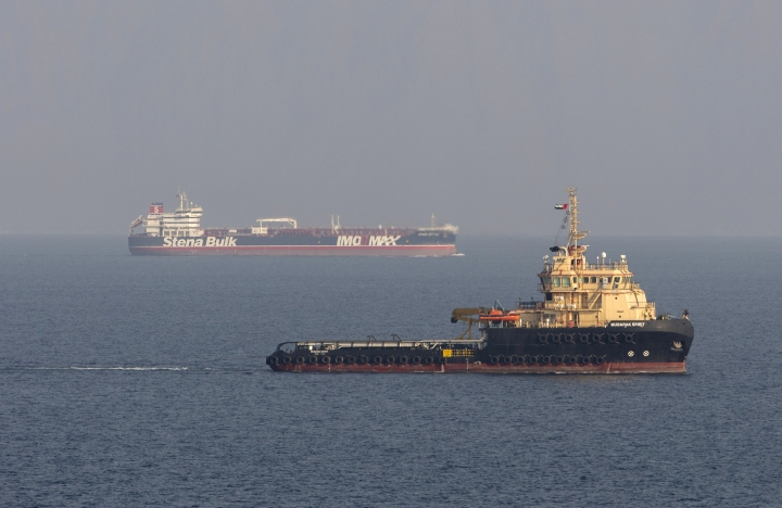 In this image taken from aboard a Royal Navy Wildcat helicopter patrolling the Gulf as part of the International Maritime Security Construct, shows the MV Stena Impero, background, as it sails from the port at Bandar Abbas, Iran, after being released by Iranian officials Friday Sept. 27, 2019. Iran on Friday released the British-flagged oil tanker it had seized in July 2019, while the country's president, returning from an annual United Nations meeting, said he had been told the United States had offered to lift sanctions if Tehran returned to the negotiating table over its nuclear program. (Dan Rosenbaum/British Royal Navy via AP)