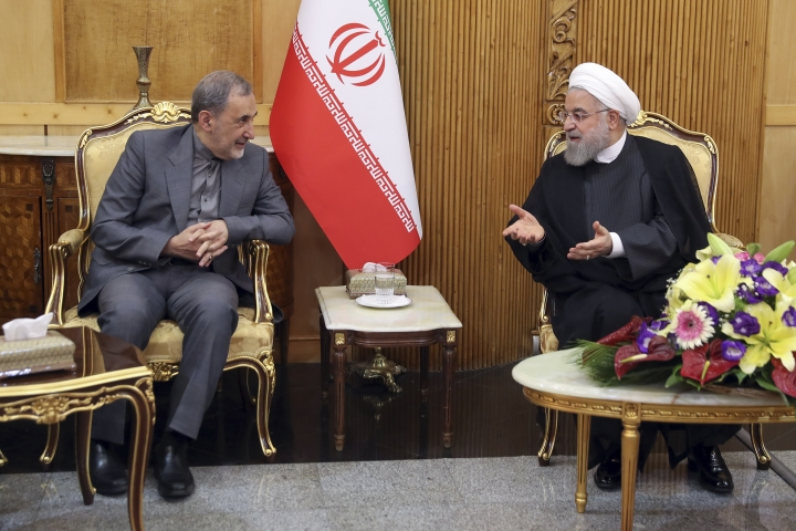 """In this photo released by the official website of the office of the Iranian Presidency, President Hassan Rouhani, right, speaks with advisor to the supreme leader, Ali Akbar Velayati, at Mehrabad airport pavilion upon arriving in Tehran from New York, where he attended the United Nations General Assembly, Iran, Friday, Sept. 27, 2019. Rouhani said U.S. sanctions on his country are """"more unstable than ever."""" (Iranian Presidency Office via AP)"""