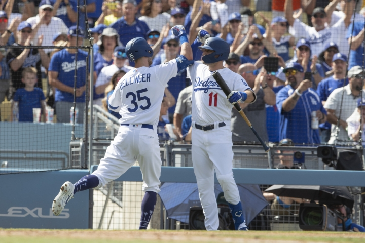 Los Angeles Dodgers' Cody Bellinger, left, gets a high forearm slam from A. J. Pollock after hitting a grand slam against the Colorado Rockies during the fifth inning of a baseball game in Los Angeles, Sunday, Sept. 22, 2019. (AP Photo/Sam Gangwer )