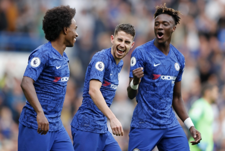 Chelsea's Jorginho, center , Chelsea's Tammy Abraham, right, and Chelsea's Willian celebrate after scoring their side's first goal during the English Premier League soccer match between Chelsea and Brighton & Hove Albion at Stamford Bridge stadium in London, Saturday, Sept. 28, 2019.(AP Photo/Frank Augstein)