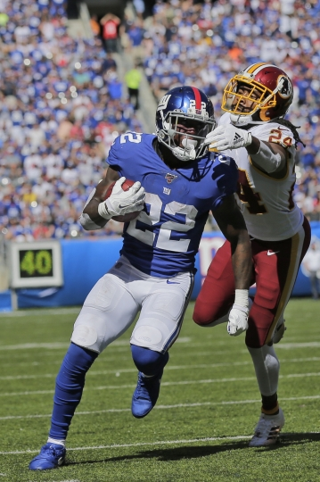 Washington Redskins' Josh Norman, right, tries to grab New York Giants running back Wayne Gallman during the first half of an NFL football game, Sunday, Sept. 29, 2019, in East Rutherford, N.J. (AP Photo/Adam Hunger)