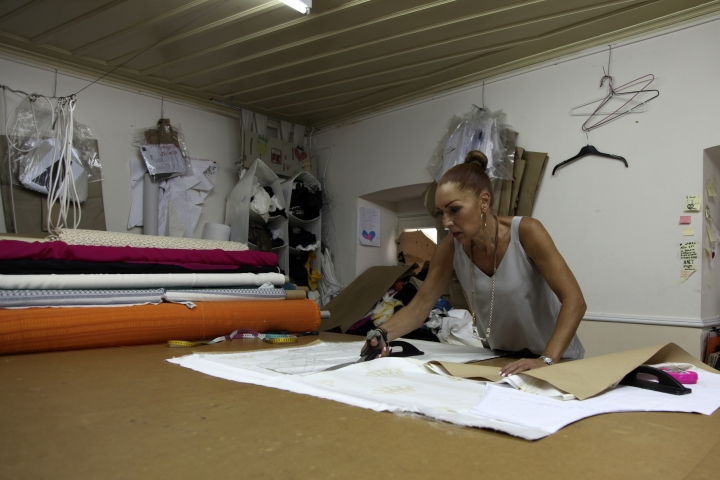 In this Wednesday, Sept. 4, 2019 photo, a seamstress works on a piece of white silk at Zeus+Dione atelier in Athens. Greece's financial crisis nearly snuffed out the country's centuries-old silk manufacturing tradition, but the end of the crippling recession has raised demand for fashion products and silk produced by a remote border town. (AP Photo/Iliana Mier)