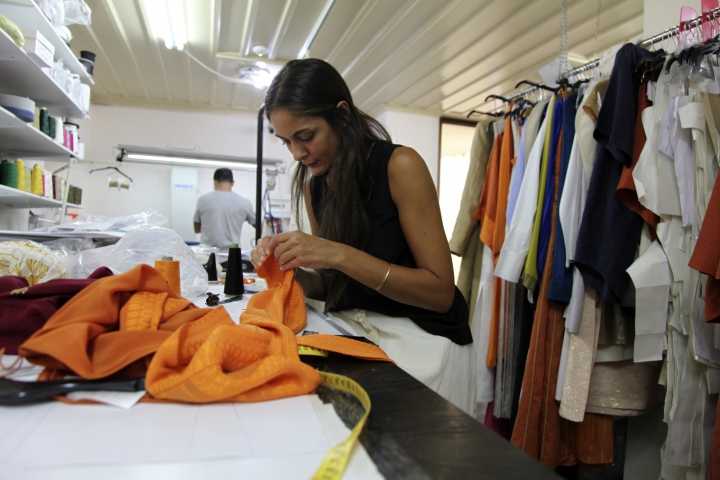 In this Wednesday, Sept. 4, 2019 photo designer Lydia Vousvouni of fashion firm Zeus+Dione works at the firms' atelier in Athens. Greece's financial crisis nearly snuffed out the country's centuries-old silk manufacturing tradition, but the end of the crippling recession has raised demand for fashion products and silk produced by a remote border town. (AP Photo/Iliana Mier)
