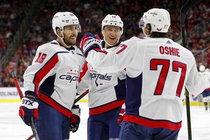 Washington Capitals' T.J. Oshie (77) celebrates his goal with teammate Chandler Stephenson (18) and Jakub Vrana (13) of Czech Republic during the first period of an NHL preseason hockey game against the Carolina Hurricanes, in Raleigh, N.C., Sunday, Sept. 29, 2019. (AP Photo/Karl B DeBlaker)