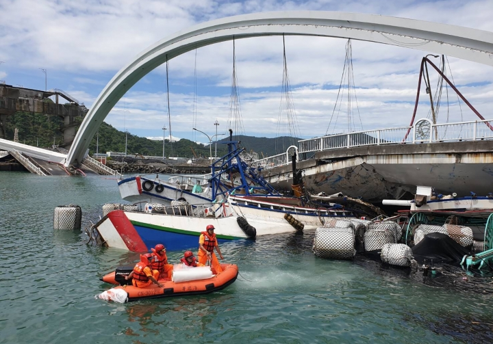 Rescuers work near the site of a collapsed bridge in Nanfangao, eastern Taiwan. Tuesday, Oct. 1, 2019. A towering bridge over a bay in eastern Taiwan has collapsed sending an oil tanker truck falling onto boats in the water below. A disaster relief official said the collapse set off a fire and at least 10 people have been hurt. (Taiwan's Coast Guard via AP)