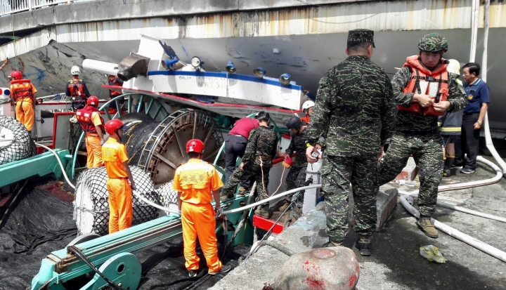 Rescuers work at the site of a collapsed bridge in Nanfangao, eastern Taiwan. Tuesday, Oct. 1, 2019. A towering bridge over a bay in eastern Taiwan has collapsed sending an oil tanker truck falling onto boats in the water below. A disaster relief official said the collapse set off a fire and at least 10 people have been hurt. (Taiwan's Coast Guard via AP)