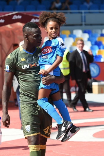 Brescia's Mario Balotelli holds his daughter Pia wearing a Napoli soccer team jersey, as he enters the pitch prior to the start of the Italian Serie A soccer match between Napoli and Brescia at the San Paolo stadium in Naples, Italy, Sunday, Sept. 29, 2019. (Cesare Abbate/ANSA Via AP)